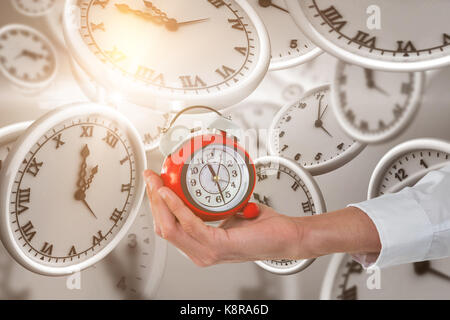 Cropped hand holding alarm clock against digitally generated image of clocks - Stock Photo