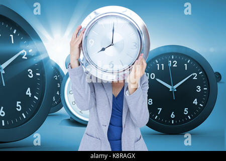 Businesswoman holding clock in front of face against digital composite image of clocks - Stock Photo