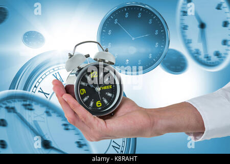 Cropped hand of male executive holding alarm clock against digitally generated image of wall clocks - Stock Photo