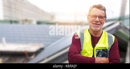 Close up portrait of senior worker wearing reflective clothing against workshop - Stock Photo