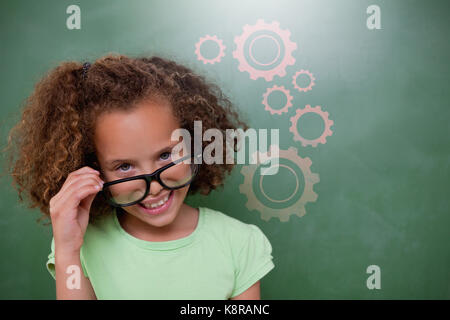 Cute pupil tilting glasses against digital composite image of gears - Stock Photo