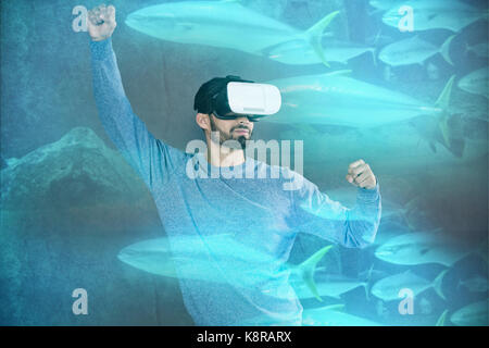 Fish swimming in a tank against man with blue shirt playing vr - Stock Photo