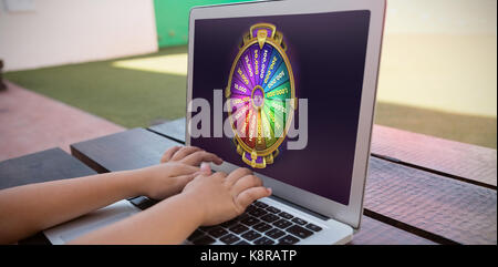 Colorful wheel of fortune on mobile screen against close up of boy using digital laptop while sitting at table - Stock Photo