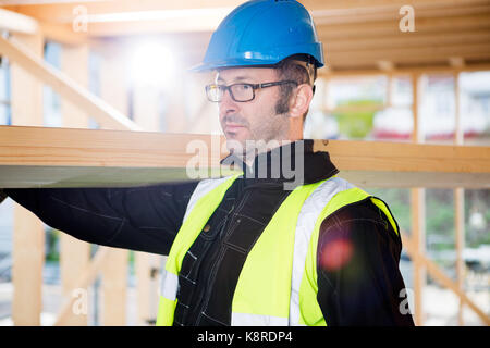 Carpenter In Protective Wear Carrying Wood On Shoulder - Stock Photo