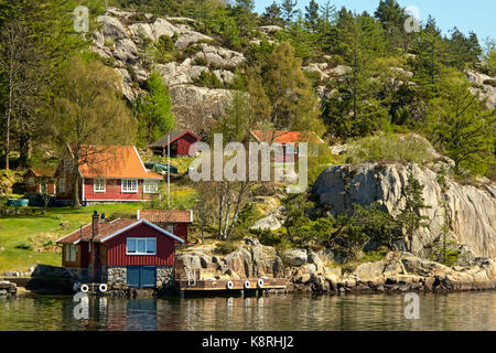 Rock coast along a Norwegian fjord with red painted wooden vacation houses on a hillside. - Stock Photo
