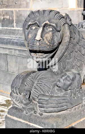 Sculpture of a lion holding a man, a detail of Bremen Cathedral, Germany - Stock Photo