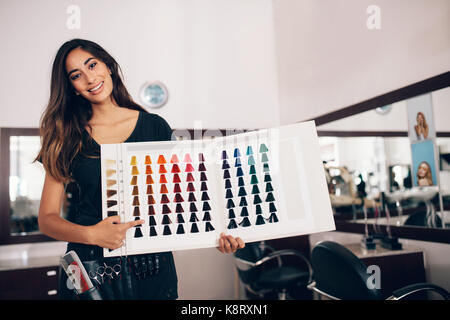 Professional woman hairdresser pointing at the hair color sample chart.  Woman with hairdressing accessories tied - Stock Photo