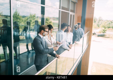 Young designers talking on break about business plans - Stock Photo