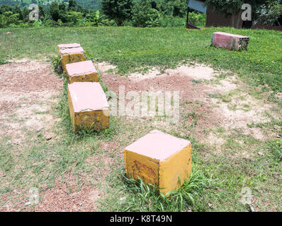 Concrete cube seat on the grass field for camping in the countryside house. - Stock Photo