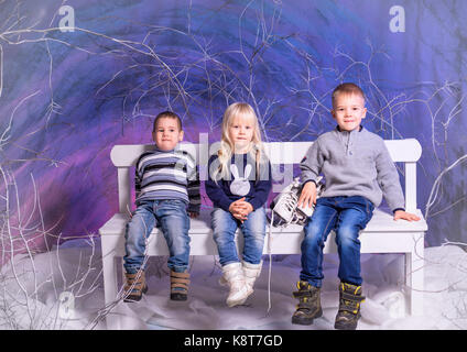 Three children sitting on bench in winter time. - Stock Photo