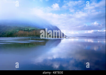 New Zealand. North Island. Low level cloud over west coast cliffs and beach. - Stock Photo
