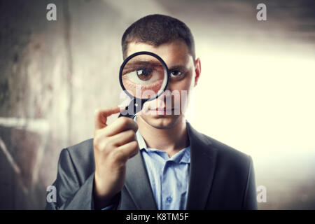 Detective looking through magnifying glass in subway tunnel. Light at End of Tunnel - Stock Photo