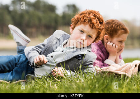 siblings lying on grass  - Stock Photo