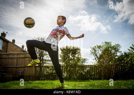 Boy playing football at home - Stock Photo