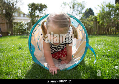 little girl playing in garden - Stock Photo