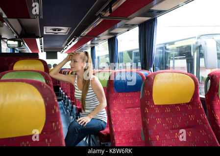 A young woman sitting comfortably on the bus. - Stock Photo
