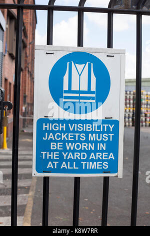 A sign on in the production company high visibility jacket must  - Stock Photo