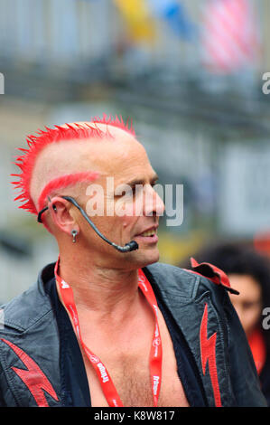 The Mighty Gareth, a male fire eater with distinctive hairstyle performing on the Royal Mile during the Edinburgh - Stock Photo