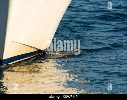 The hull of a white boat with a blue stripe cuts slowly through the water with  the white reflecting of the myriad - Stock Photo