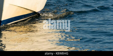 A small wave shows how the white hull of a small boat cuts through small ripples in the water surface. - Stock Photo