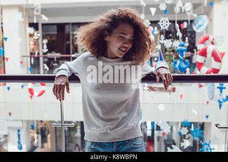 Curly haired girl with freckles in blank grey sweatshirt. Mock up. - Stock Photo