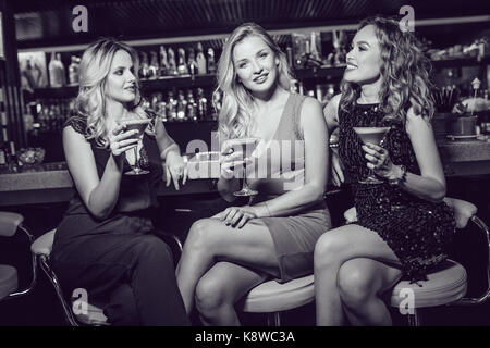 Beautiful women are sitting on the bar and drinking cocktails. - Stock Photo