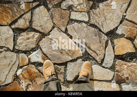 Male feet standing on the paved street in beige shoes. Top view. - Stock Photo