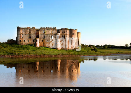 A view of Carew castle, Pembrokeshire, wales, UK. Taken in the evening in golden sunlight with the castle reflected - Stock Photo