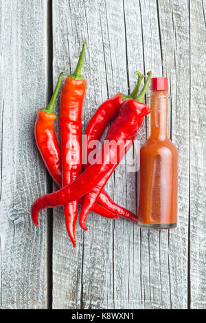 Red chili peppers and chili sauce. Top view. - Stock Photo