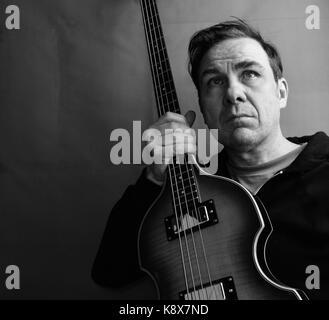 Man holding bass guitar - Stock Photo