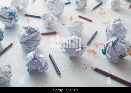 Close-up of crumpled paper balls on a white wooden background with pencils and pencil shavings. Creative writing - Stock Photo