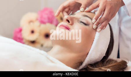 Beautiful woman relaxing during rejuvenating facial massage in a - Stock Photo
