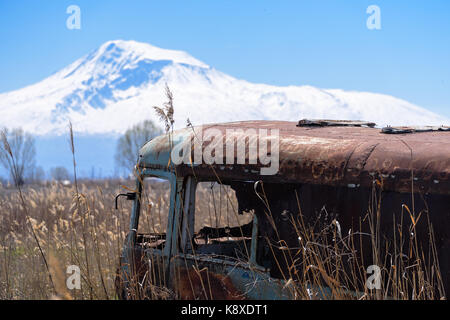 Abandoned and rusty old Soviet Russian bus in the middle of reeds and agriculture fields with snow-capped scenic - Stock Photo