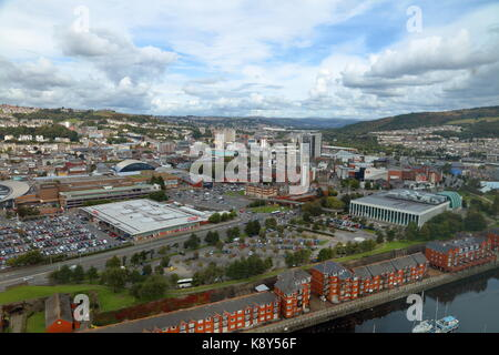 Looking out across Swansea city over the rooftops towards the valleys with supermarket car park and a liesure centre - Stock Photo