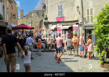 Tourists relaxing in the sunshine along a cobbled street in the medieval French fortified city of Carcassonne, La - Stock Photo