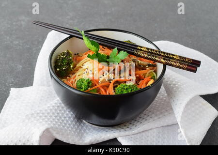 Rice noodles with carrot, broccoli and mushrooms in a black bowl on a black abstract background. Asian food. Healthy - Stock Photo