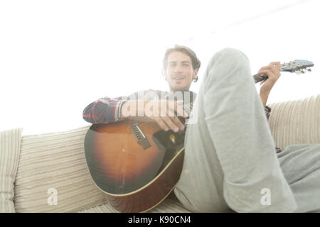 guy with guitar sitting on sofa in living room. concept of a lifestyle - Stock Photo