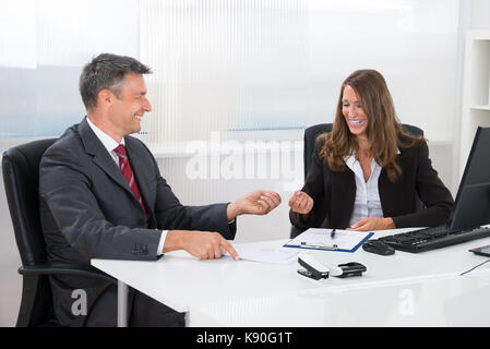 Two Businesspeople Exchanging Blank Visiting Card At Desk In Office - Stock Photo
