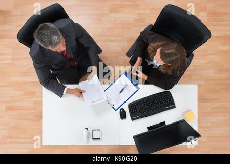 High Angle View Of Two Businesspeople Discussing On Documents In Office - Stock Photo