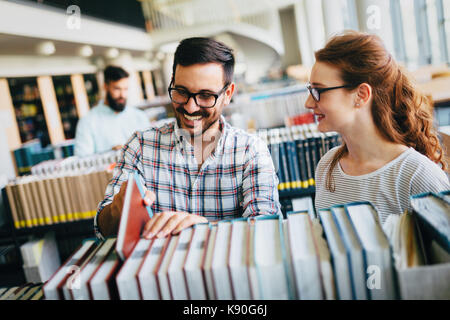 Young attractive students spending time in library