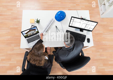 High Angle View Of Two Architects Discussing Blueprint In Office - Stock Photo
