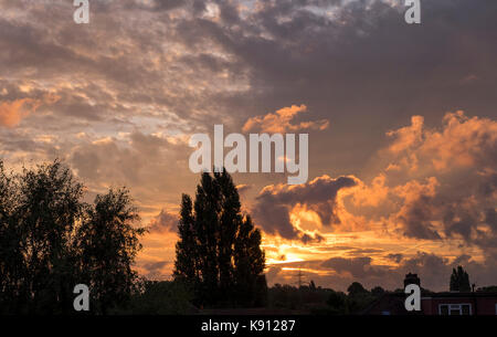 Wimbledon, London, UK. 21st Sep, 2017. Sun rises behind dramatic autumn sky with multiple cloud formations and vapour - Stock Photo