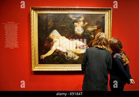 Two women looking at the oil painting 'Sleeping Bacchante' (around 1680-1685) by Gerard de Lairesse at the exhibition - Stock Photo