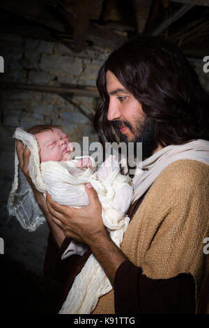 Live Christmas nativity scene in an old barn - Reenactment play with authentic costumes.  The baby is a (property - Stock Photo