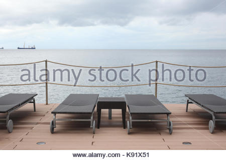 sunbeds on afront sea  wooden deck in an overcast day - Stock Photo