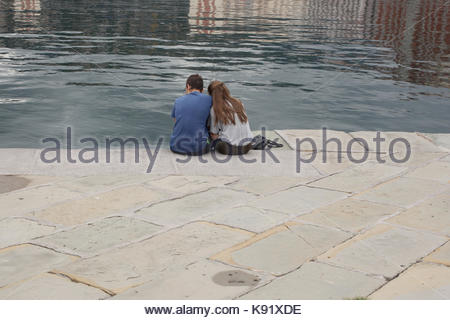 young couple in love sitting on the edge of a stone pier in Trieste Italy - Stock Photo