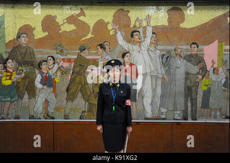 09.08.2012, Pyongyang, North Korea, Asia - A platform guard stands in front of a huge propaganda mural inside a - Stock Photo