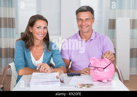 Portrait Of A Smiling Couple Calculating Bills At Home - Stock Photo
