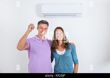 Portrait Of Happy Couple Standing In Front Of Air Conditioner With Remote In Man's Hand - Stock Photo