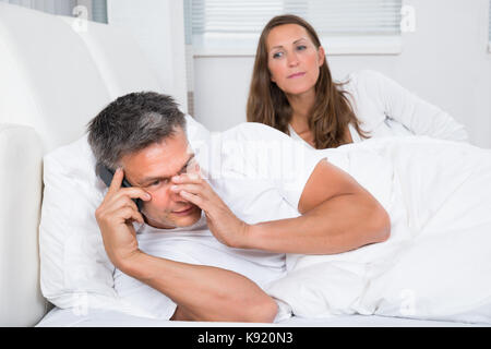 Woman Looking At Man Talking On Mobile Phone In Bedroom - Stock Photo